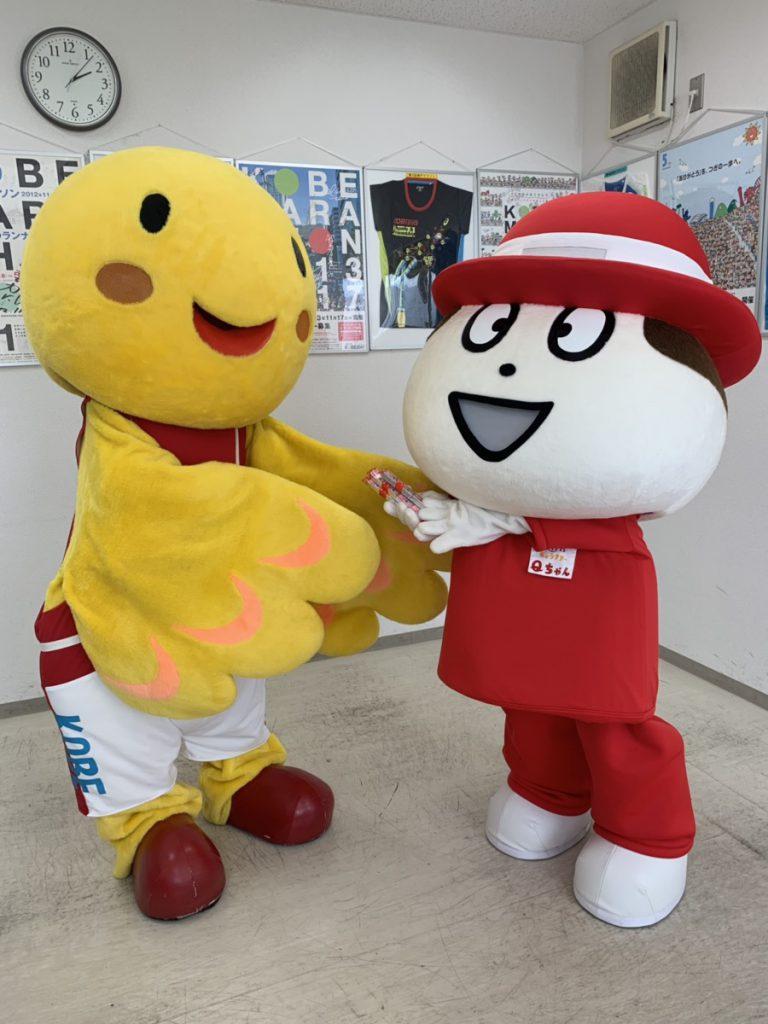 QBBのQちゃんが兵庫県マスコットのはばたんに、QBBベビーチーズをプレゼントしています。