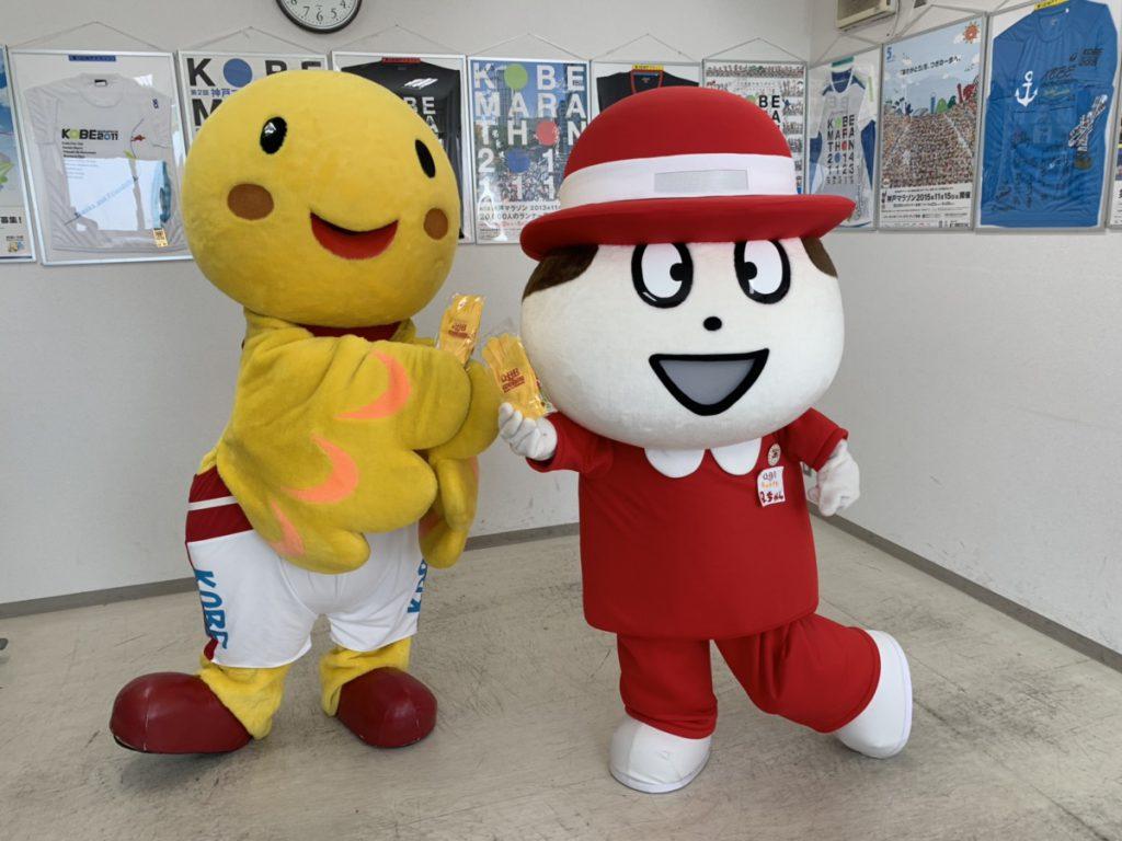 兵庫県マスコットはばたんとQBBマスコットQちゃんが神戸マラソンで配布するグローブをもっています