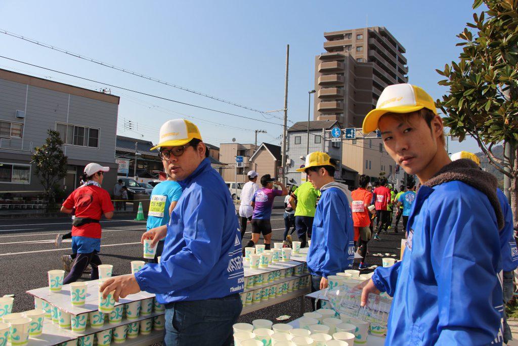 神戸マラソンの須磨給水所にて、ランナーに水を配るボランティアスタッフの様子