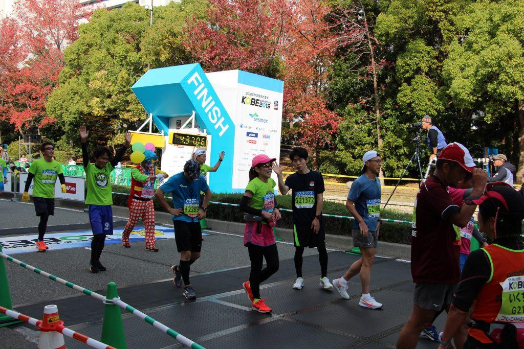 神戸マラソンのゴール直後にピースサインをするQBBランナー。