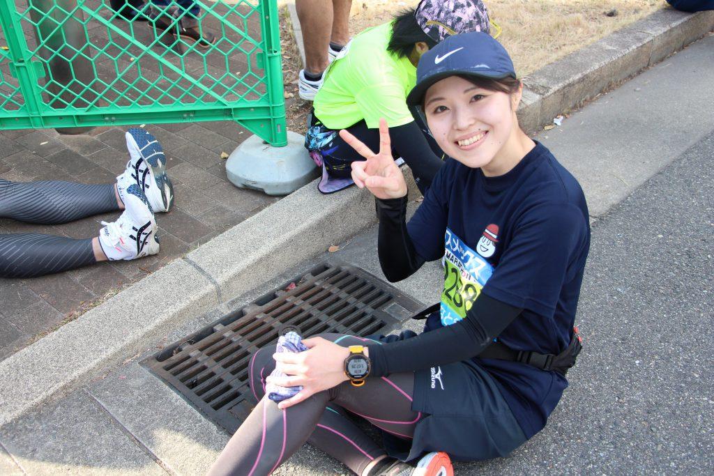 ゴール直後に疲れて座り込む神戸マラソンランナー