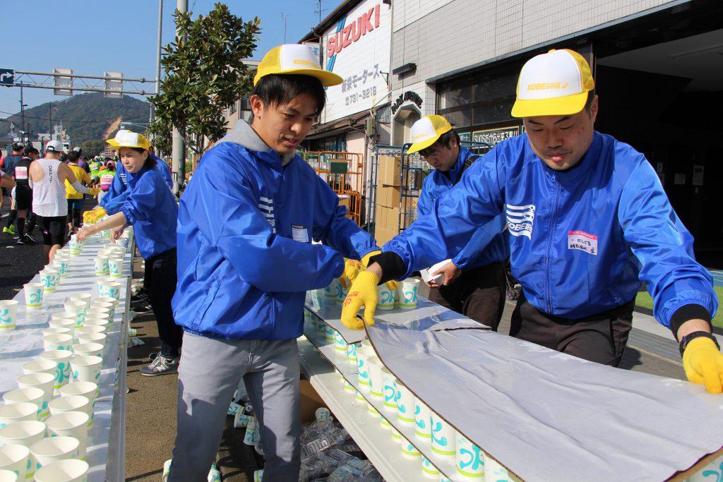 前を見ることもできず、ひたすら給水作業に励むボランティアスタッフ(神戸マラソンにて)