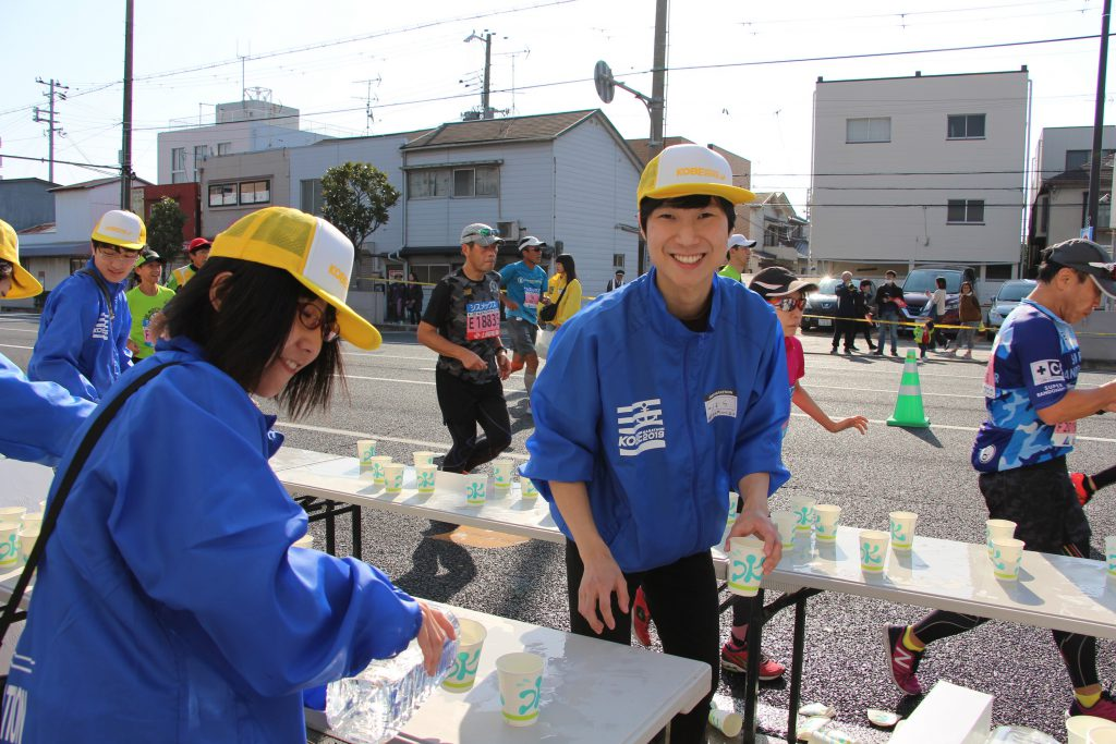 ハードワークでも笑顔で給水をするボランティアスタッフ(神戸マラソンにて)